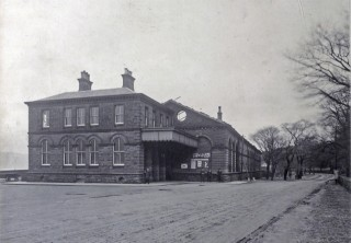 The front of the first station building of 1865, shortly before its demolition in 1903. The roof of the train shed has been dismantled. A service was maintained throughout the building of the new station.